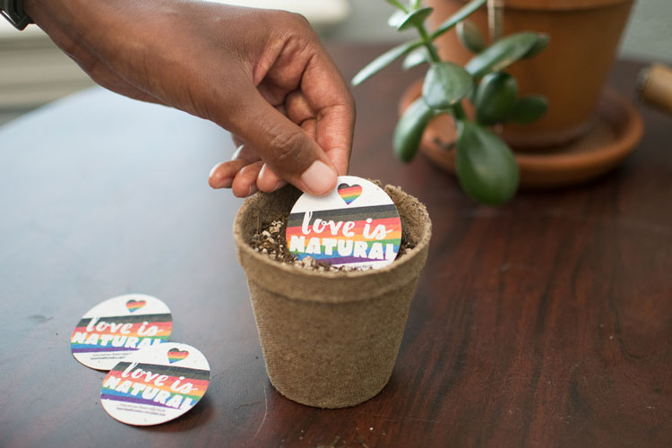 """love is natural"" seed paper pin being planted"